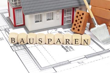 Bauplan mit Ziegelstein und Haus mit Bausparen