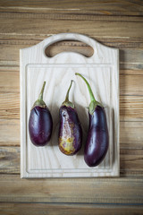 Three ripe eggplant on a chopping board