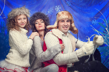 Happy family in winter hat, gloves and sweater in studio.