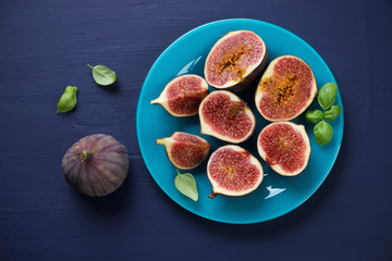 Sliced figs on a plate, above view, dark blue wooden surface