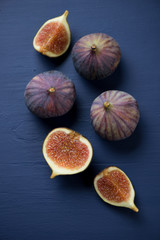 Ripe figs over dark blue wooden background, studio shot