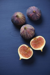 Whole and sliced ripe fig fruits over dark blue wooden surface