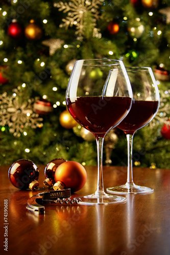 Glasses of red wine on table with Christmas tree - 74390688