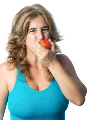 Sporty hispanic woman eating a fresh tomato