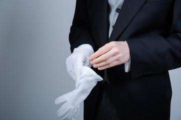 Butler mit weißen Handschuhen anziehend