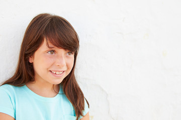 Smiling Young Girl Standing Outdoors Against White Wall
