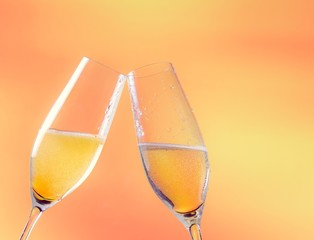 two flutes of champagne with golden bubbles and space for text