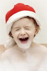 Little laughing Santa in the bath full of foam