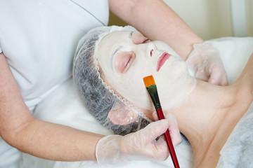 Spa cosmetologist applying facial mask