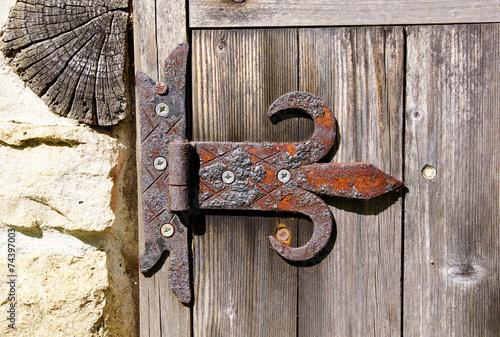 Old rusty hinge on wooden door - 74397003