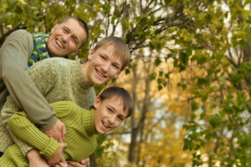 Father and sons in autumn park