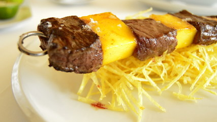 Skewer of mango fruit and meat of cow or beef at grill