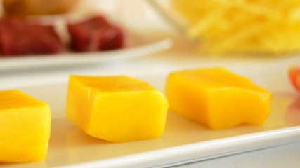 Cubes of mango fruit in a kitchen table with meat