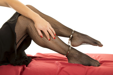 Woman legs black fishnet cuffs on ankles hand on leg