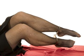 Woman legs blck fishnet cuffs on ankles