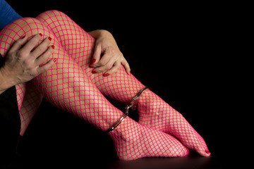 Woman legs in pink fishnet with cuffs on ankles hands