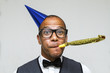 Young geek celebrating with party blower and hat