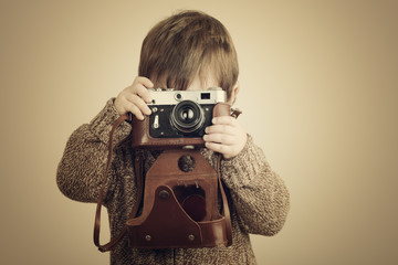 Little boy with an old camera