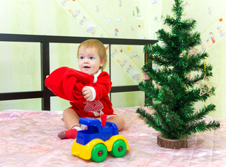 Baby boy playing with Santa Claus hat at home