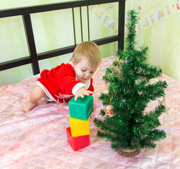 Gifted little child building tower of bricks near new year fir