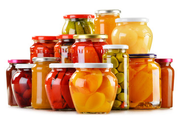 Jars with fruity compotes jams and pickled vegetables isolated