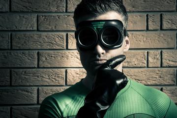 Confident superhero against a brick wall