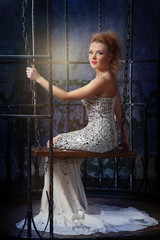 red-haired model in long evening dress sitting in a half-turn