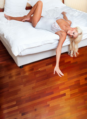 Beautiful woman lying on bed. Parquet floor