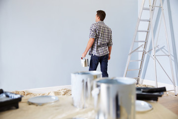 Man Decorating Nursery For New Baby