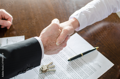Estate agent shaking hands with his customer - 74404079