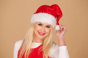 Cute blond girl in a festive red Santa hat