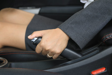 Woman pulling the hand brake in car