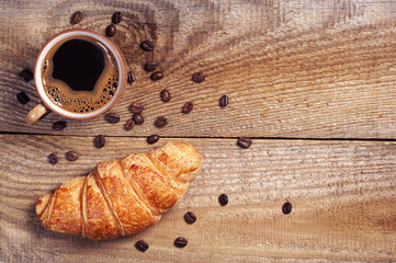 Cup of hot coffee with croissant