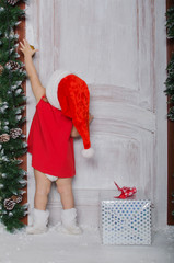 Child dressed as Santa with gift opens door
