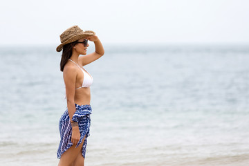 woman standing at beach and looking far way