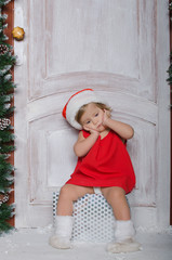Child dressed as Santa is sitting on box