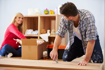 Couple Preparing To Assemble Flat Pack Furniture In Nursery