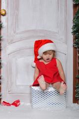 Baby dressed as Santa is sitting on box and sings