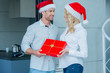 Couple Wearing Santa Hats Exchanging Gift