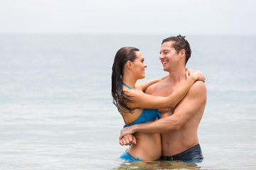 young couple embracing in the ocean