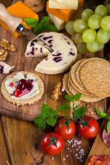 soft cheese with fruits, oat crackers and basil