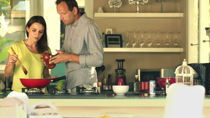 Young couple cooking, adding sauce in kitchen at home
