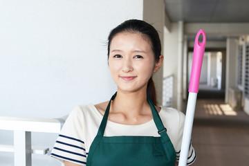 掃除用具を持つ笑顔の主婦