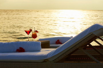 Loungers At Edge Of Tropical Sea With Cocktails