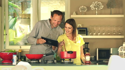 Happy couple using tablet computer and cooking in kitchen