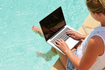 Woman Using Laptop Whilst Dangling Feet In Swimming Pool