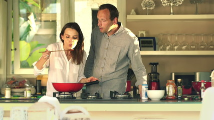 Young couple cooking and tasting prepared sauce in kitchen