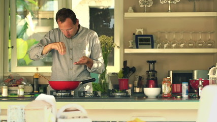 Handsome man cooking and adding seasoning in kitchen