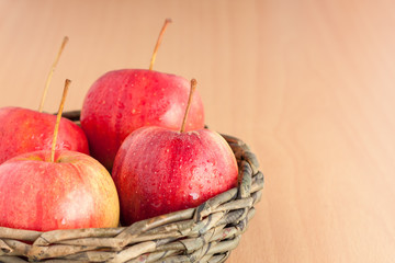 Ripe four red apple in the basket on plywood background