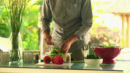 Young, handsome man mixing salad in kitchen at home